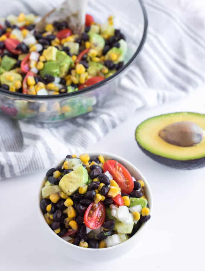 Serving of black bean and corn salad with avocados, tomatoes, onion, and cucumbers.